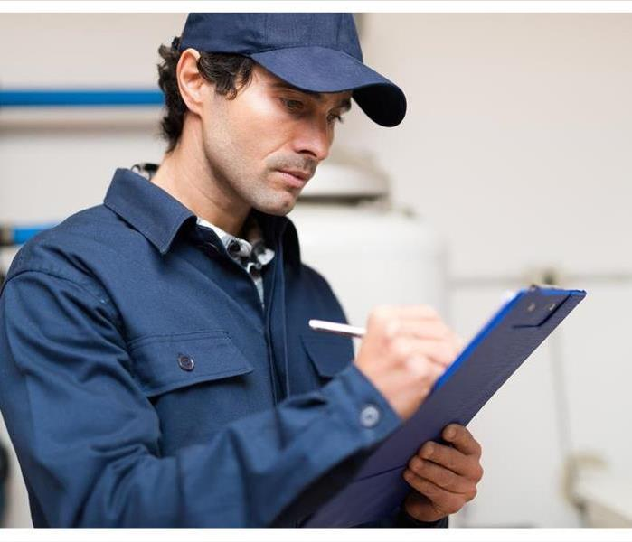 A plumber in a blue cap writing on a clipboard